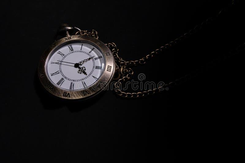 Klockan b?r en antik p?se som f?rl?ggas p? en svart bakgrund arkivfoto