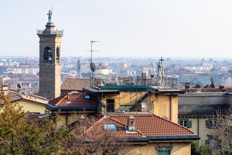 klockatorn av kyrkan över stads- hus av Bergamo arkivfoton