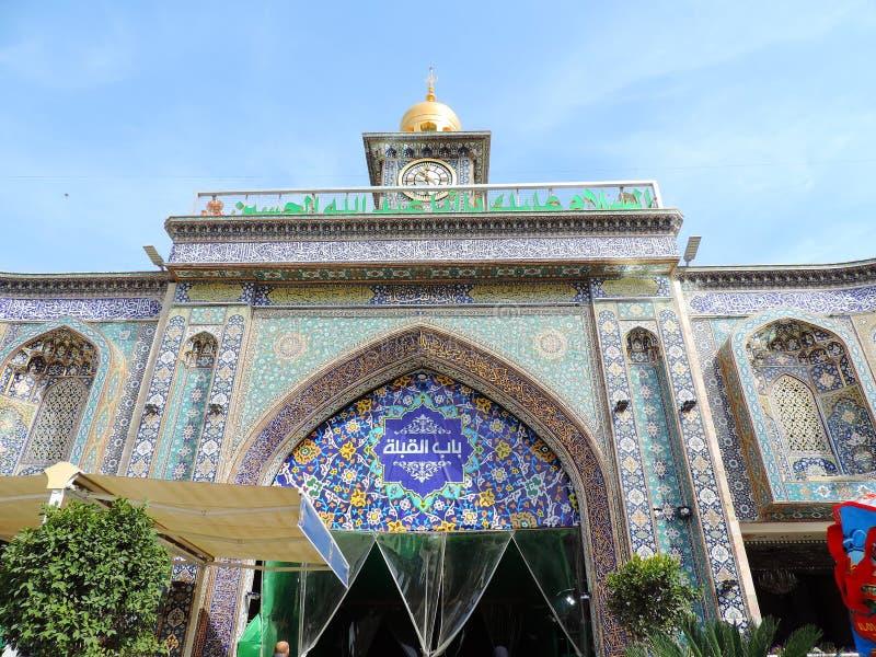 Klockatorn på ingången av den heliga relikskrin av Husayn Ibn Ali, Karbala, Irak royaltyfria foton