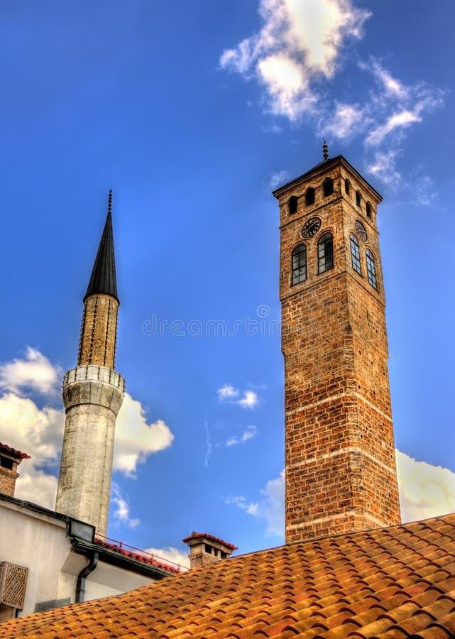 Klockatornet och Gazi Husrev-tigger moskén royaltyfri fotografi