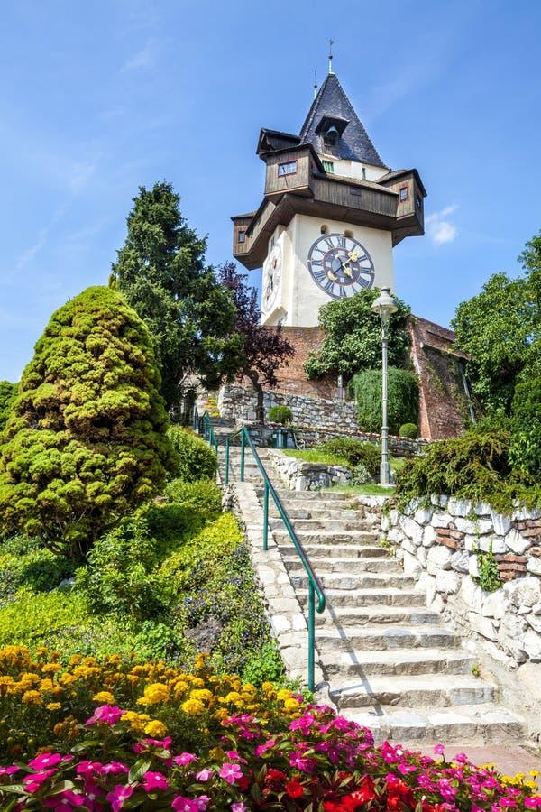 Klockatornet (Uhrturmen) och blommaträdgård Österrike graz arkivbilder