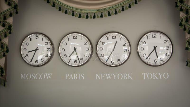 Klockor på en vägg med tidszonen av det olika landet royaltyfri bild