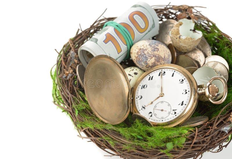 Klockor, pengar och ägg i ett rede arkivfoton