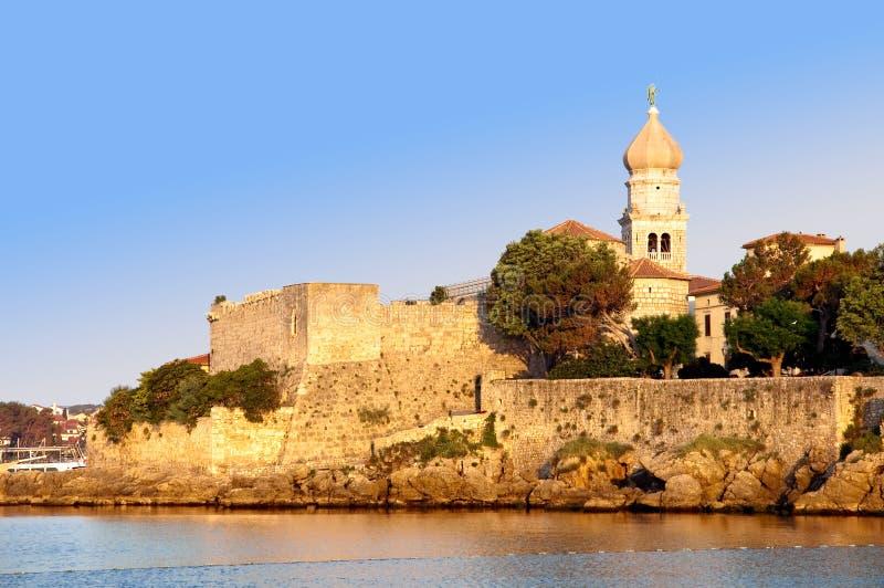 Klockstapel och gammala townväggar vid havet på krk - Kroatien arkivbilder
