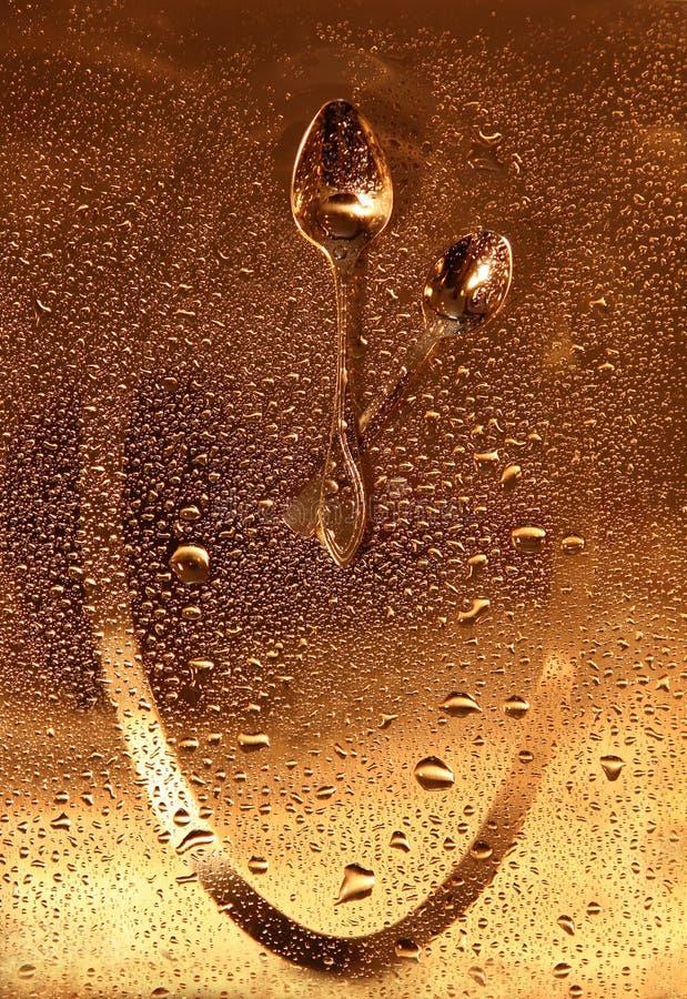 Klok die van 2 lepels op gouden oppervlakte met dalingen wordt gemaakt royalty-vrije stock foto