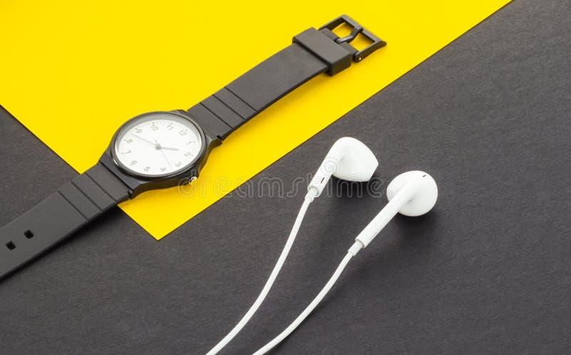 Klok en hoofdtelefoons op een gele zwarte achtergrond, close-up stock foto's