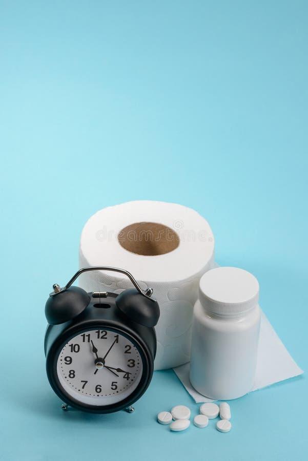 Klok, toiletpapier en pillen stock fotografie