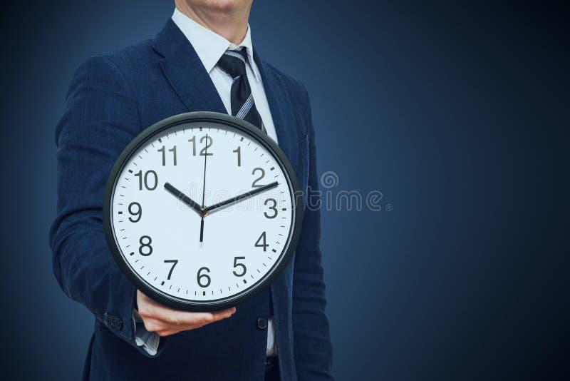 Klok in zakenmanhand Zakenman met een klok in een hand Zakenman met klok op tijd concept stock foto's