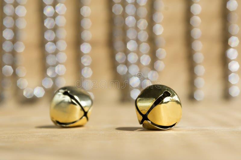 Klokken van het Kerstmis de gouden kenwijsje op glanzende bezinningen als achtergrond, zilveren Kerstmisketen, houten lijst royalty-vrije stock foto