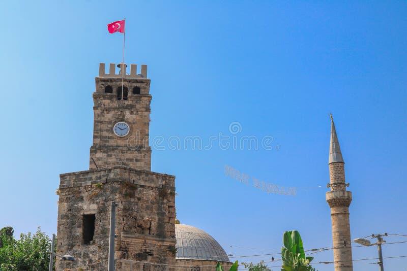 Klokketoren en moskee met minaret op achtergrond Antalya, Turkije royalty-vrije stock foto