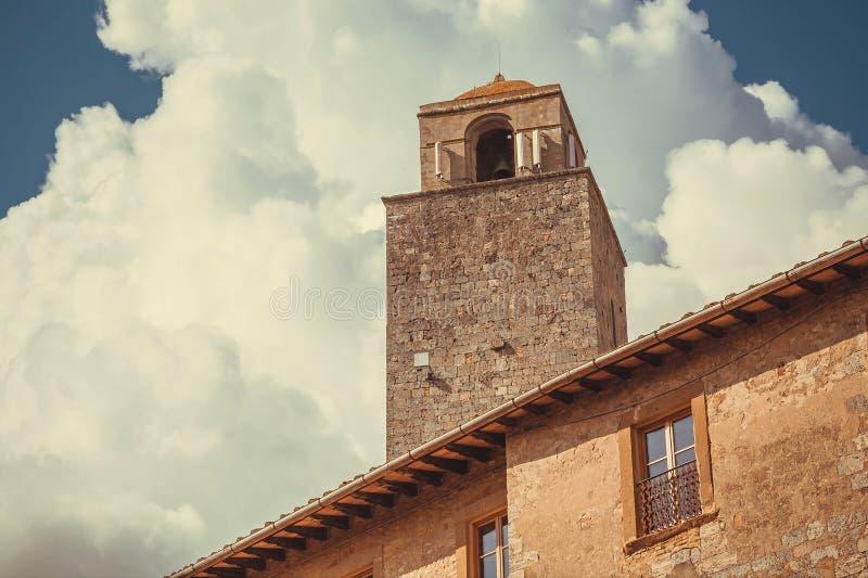 Klokketoren onder witte wolken blauwe hemel in historische Italiaanse stad stock foto