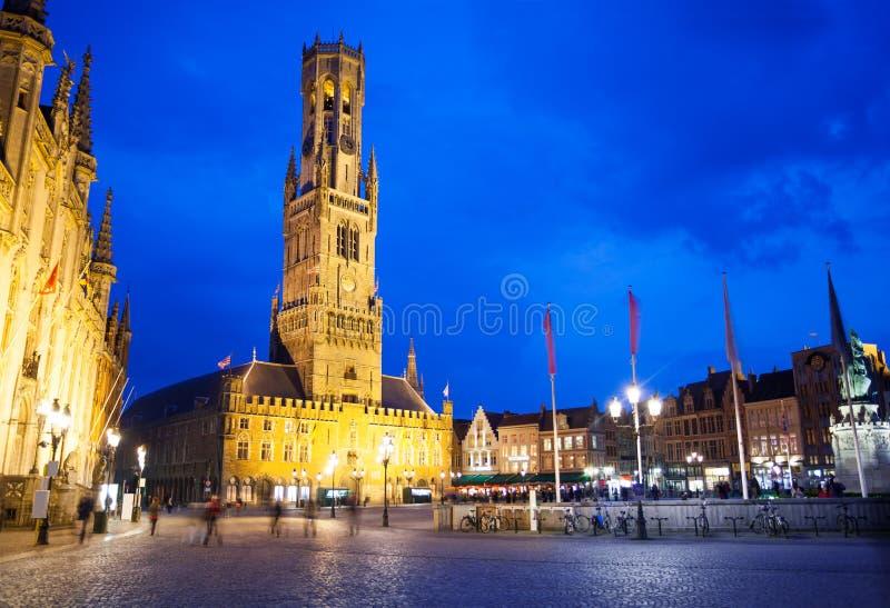 Klokketoren van Brugge en Grote Markt bij nacht stock afbeeldingen