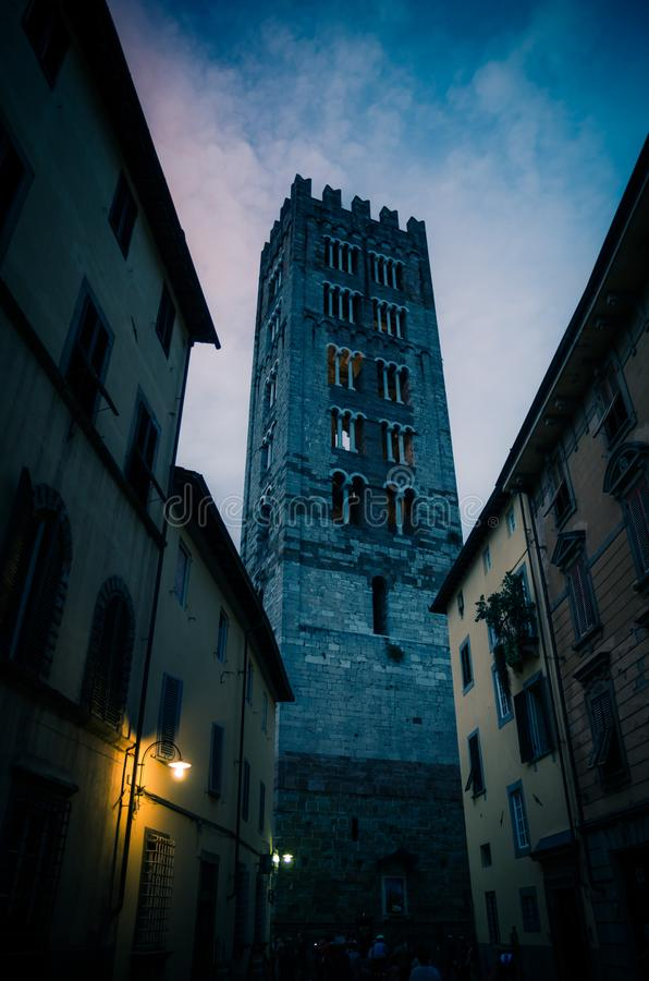 Klokketoren van Chiesa Di San Frediano katholieke kerkmening door smalle straat met lamplicht in historisch centrum van oude medi stock foto