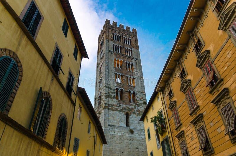 Klokketoren van Chiesa Di San Frediano katholieke kerkmening hieronder van smalle straat in historisch centrum van oude middeleeu royalty-vrije stock foto's