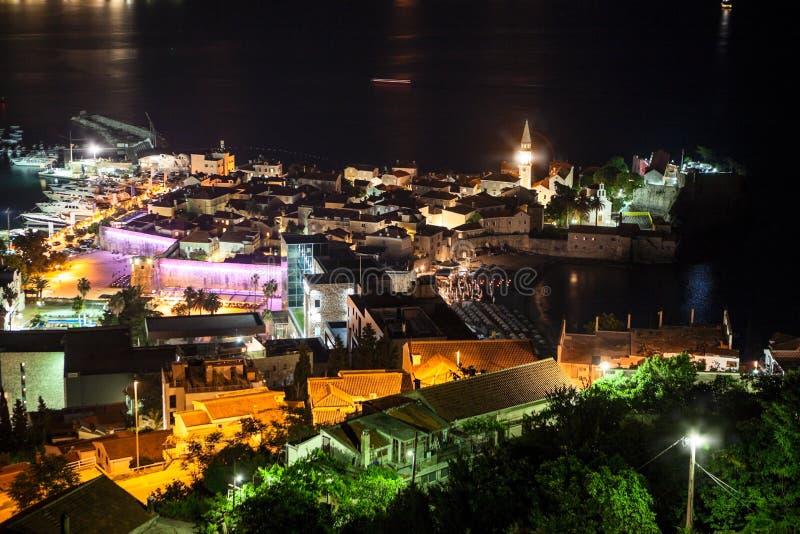 Klokketoren van de Oude Stad van Budva-stad en het strand van Ricardova Glava bij nacht Satellietbeeld met huizendaken ADRIATISCH stock afbeeldingen