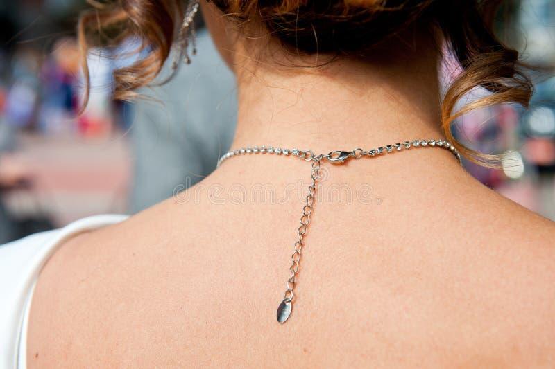 Klonkedjehalsband på en ung flickas nacke arkivbild