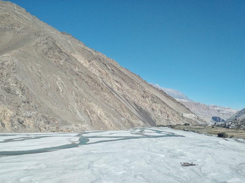 Kloof van de Kali Gandaki-rivier met hoge klippen en de vallei met een shepard die zijn geiten en schapen leiden stock foto's