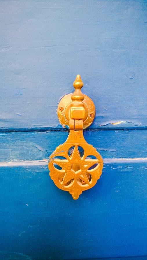 Kloppers van het Birght de gele messing op een trillende blauwe deur, Marokko royalty-vrije stock fotografie
