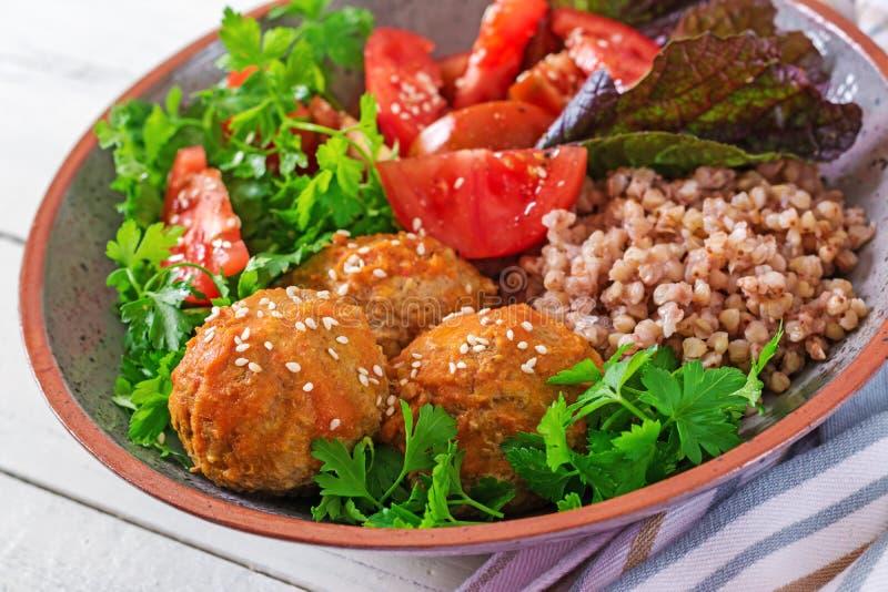 Klopsiki, sałatka pomidory i gryczana owsianka na białym drewnianym stole, zdrowa żywność Dieta posiłek Buddha puchar obrazy royalty free