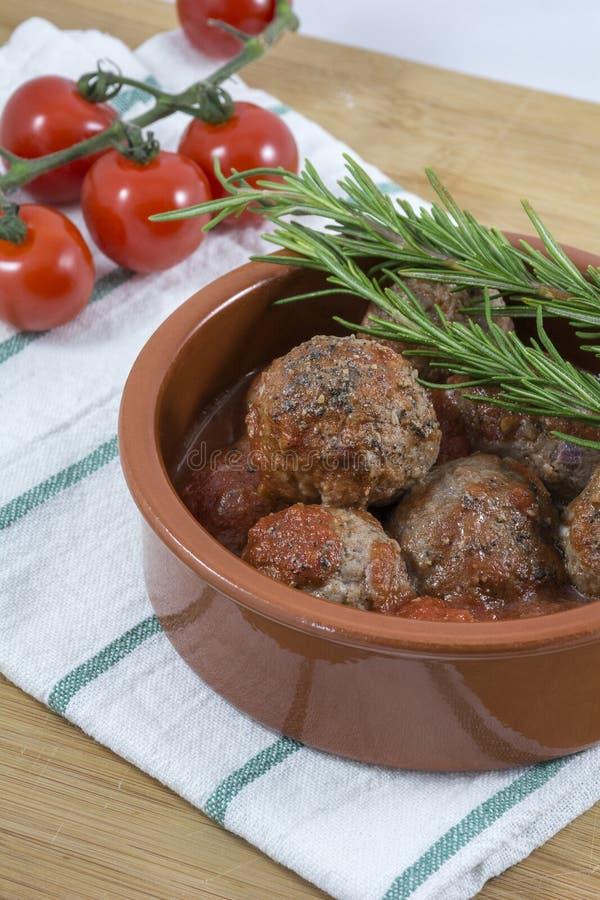 Klopsiki z pomidorowym kumberlandem, czerwoną wiśnią i rozmarynami na białym kuchennym ręczniku, fotografia stock