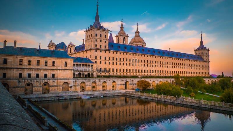 Kloster och kunglig personstället El Escorial i Spanien på solnedgången med reflexion i ett damm royaltyfria foton