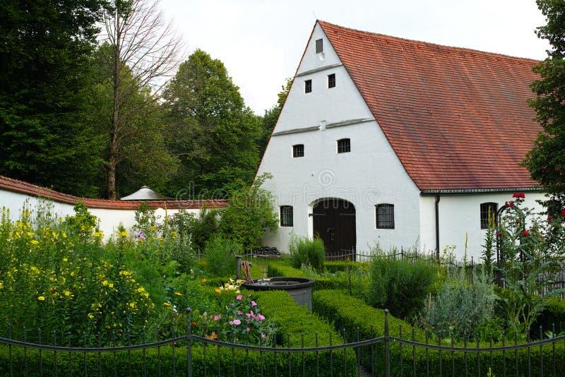 Klosterträdgårdidyll med den väl vita byggnad och väggen royaltyfri foto