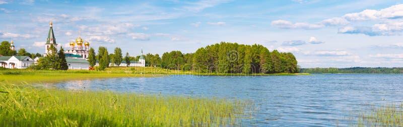 Klosterwand und -türme auf Ufer von See lizenzfreies stockfoto