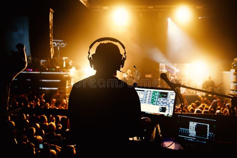 Klubba diskodiscjockey som spelar och blandar musik för folkmassan av lyckligt folk arkivfoton