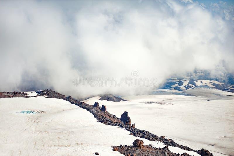 Klubbor av dimma och moln fortskrider lutningen av Mount Elbrus arkivfoton
