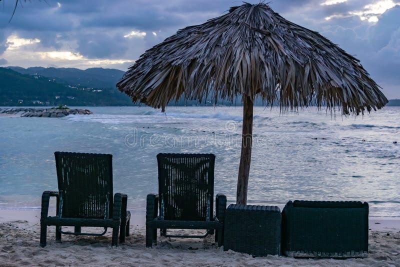 Klubsessel und ein Stroh decken Dachregenschirm durch den Strand mit Stroh stockfoto