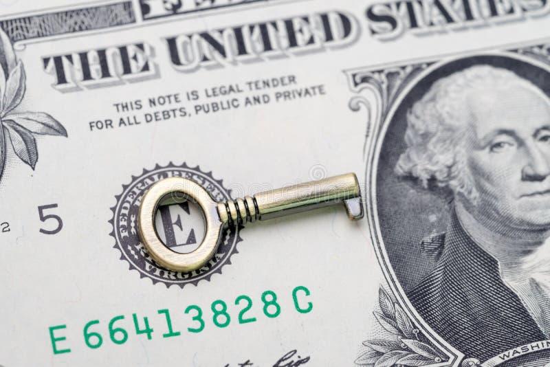 Klucz sukces w inwestorskim i pieniężnym planie, zamkniętym w górę metalu brązu małego klucza na dolara amerykańskiego pieniądze  zdjęcie royalty free