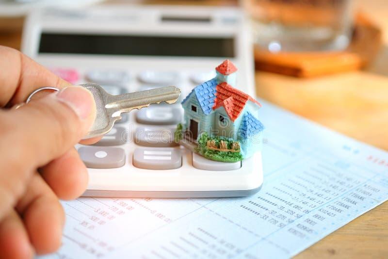 Klucz w ręce z domu kalkulatorem na książkowym banku i modelem fotografia stock