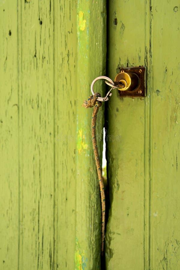 Klucz z zespołem na zielonym drzwi zdjęcie stock