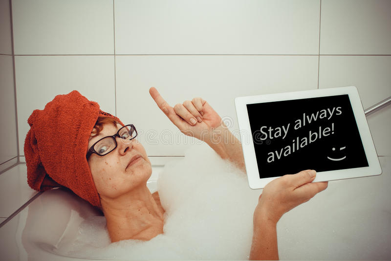 Kluge Frau in der Badewanne mit Tablet-Computern, Raum für Text stockbilder