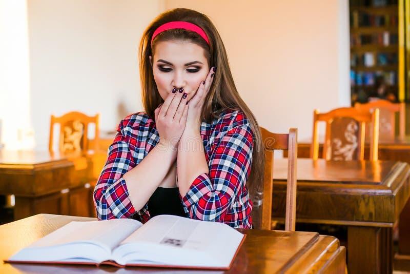 Kluge Studentin überraschte das Mädchen, das in der Bibliothek mit Büchern sitzt lizenzfreie stockfotografie