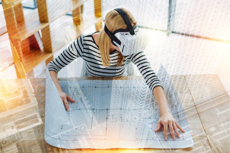Kluger Ingenieur, der mit einem Entwurf beim allein arbeiten sitzt stockbilder