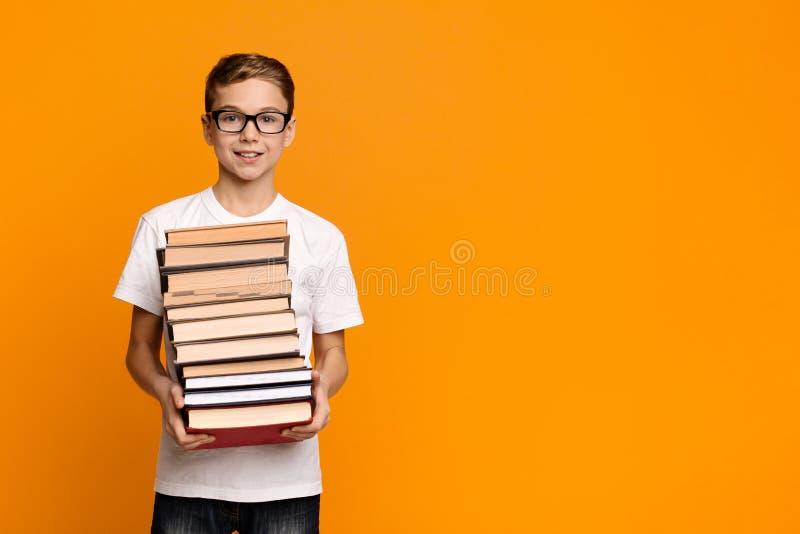 Kluger jugendlich Junge in den Gläsern, die Stapel Bücher halten stockfotografie