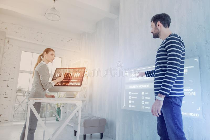 Kluger Programmierer, der auf den Schirm bei der Unterhaltung mit seinem Kollegen zeigt stockfotos