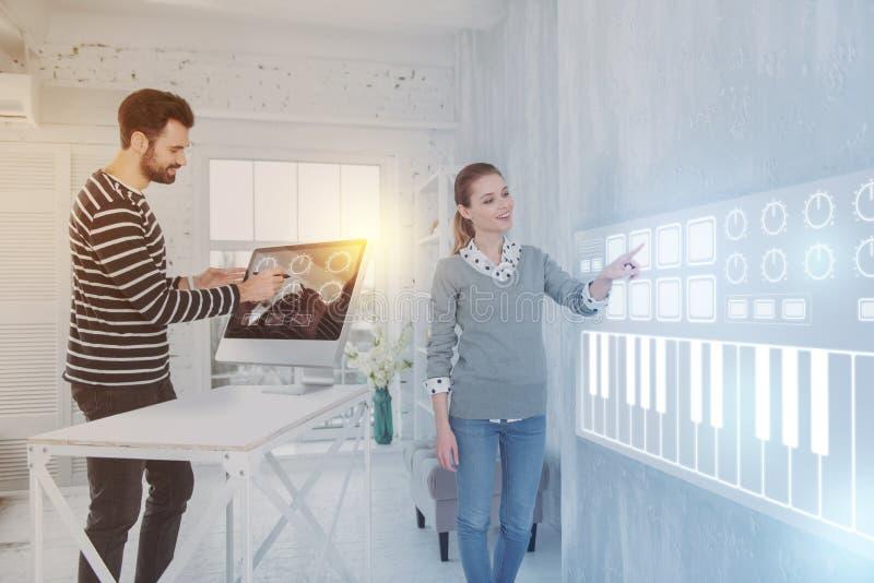 Kluger Programmierer, der auf den Schirm beim Arbeiten mit einem Kollegen zeigt stockfoto