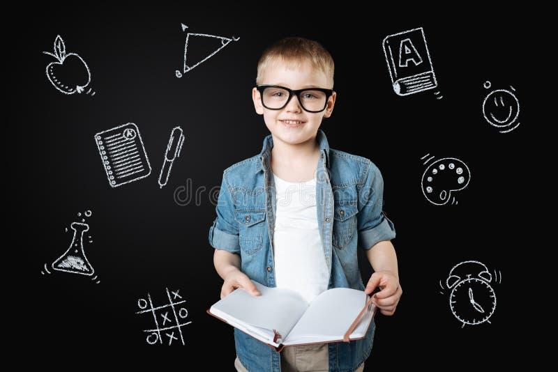 Kluger Schüler, der ein Notizbuch hält und zur Lektion fertig wird stockfotos