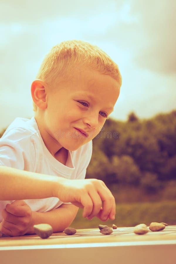 Kluges Kind des kleinen Jungen, das Kontrolleure im Park spielt lizenzfreie stockfotos