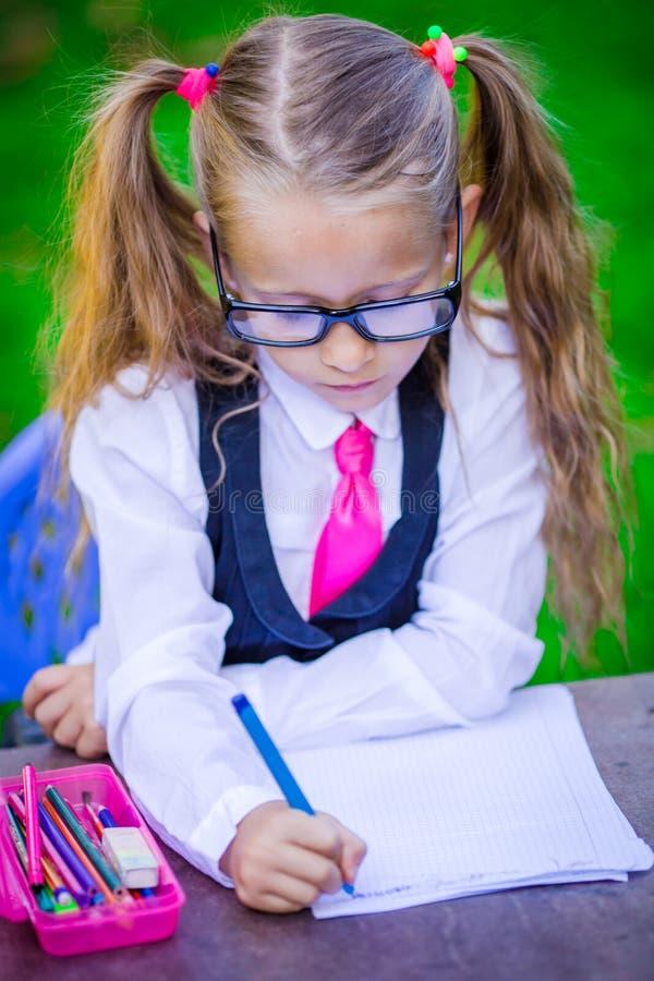 Kluges kleines Schulmädchen am Schreibtisch mit Anmerkungen und lizenzfreies stockfoto