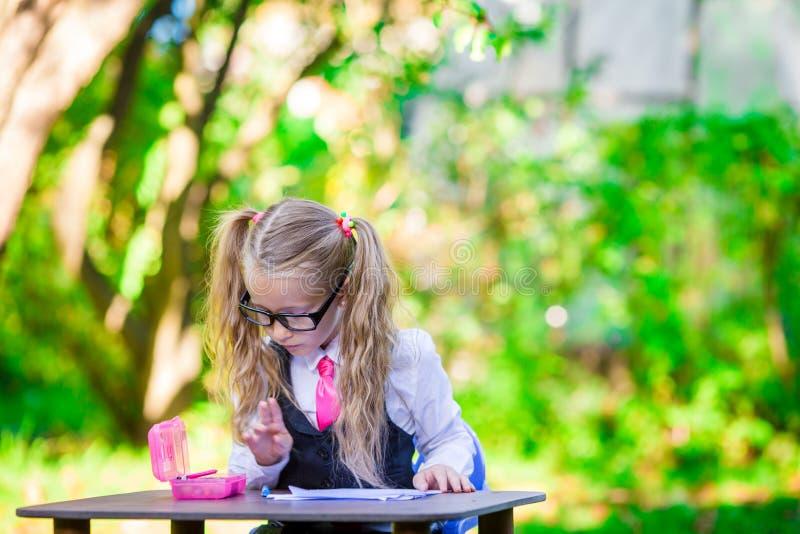 Kluges kleines Schulmädchen am Schreibtisch mit Anmerkungen und stockbilder
