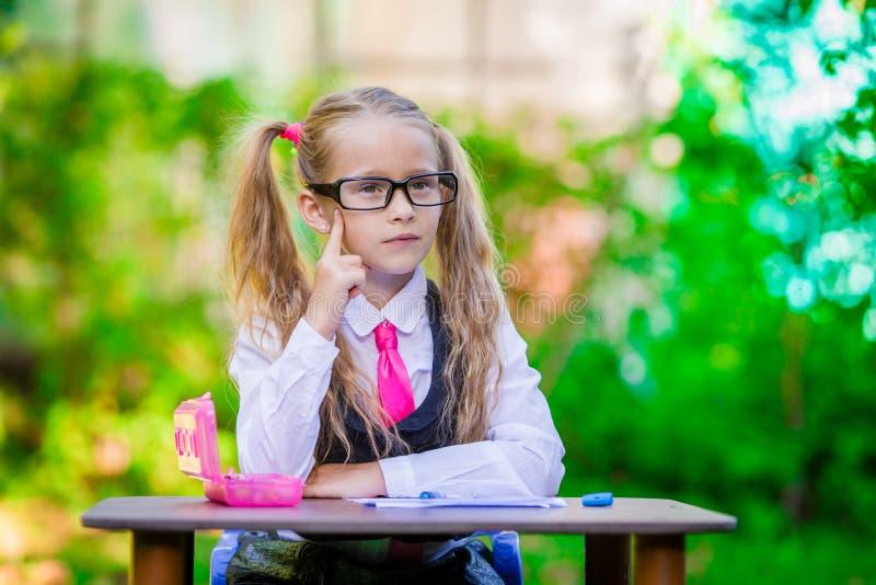 Kluges kleines Schulmädchen am Schreibtisch mit Anmerkungen und lizenzfreie stockbilder