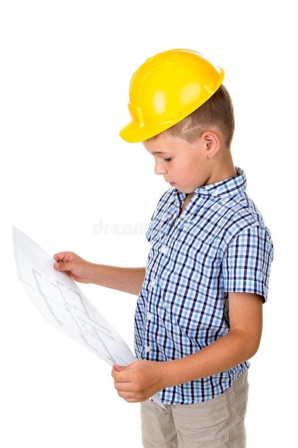 Kluges Kleinkind im gelben Sturzhelm und das blaue karierte Hemd, das ein Gebäude hält, tapezieren Plan in den Händen, lokalisier stockbilder