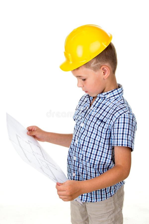 Kluges Kleinkind im gelben Sturzhelm und das blaue karierte Hemd, das ein Gebäude hält, tapezieren Plan in den Händen, lokalisier stockfoto
