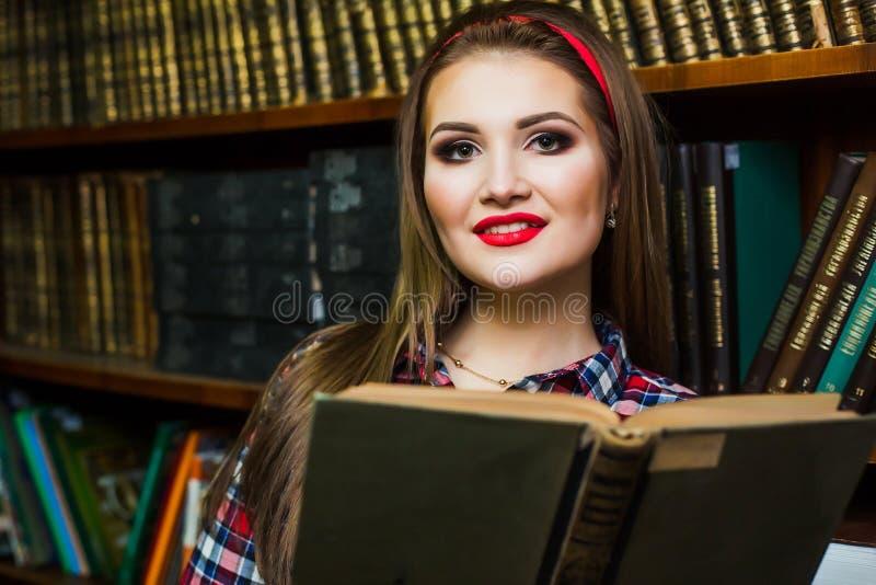 Kluges Studentinmädchen, das in der Bibliothek mit Büchern sitzt lizenzfreie stockfotos