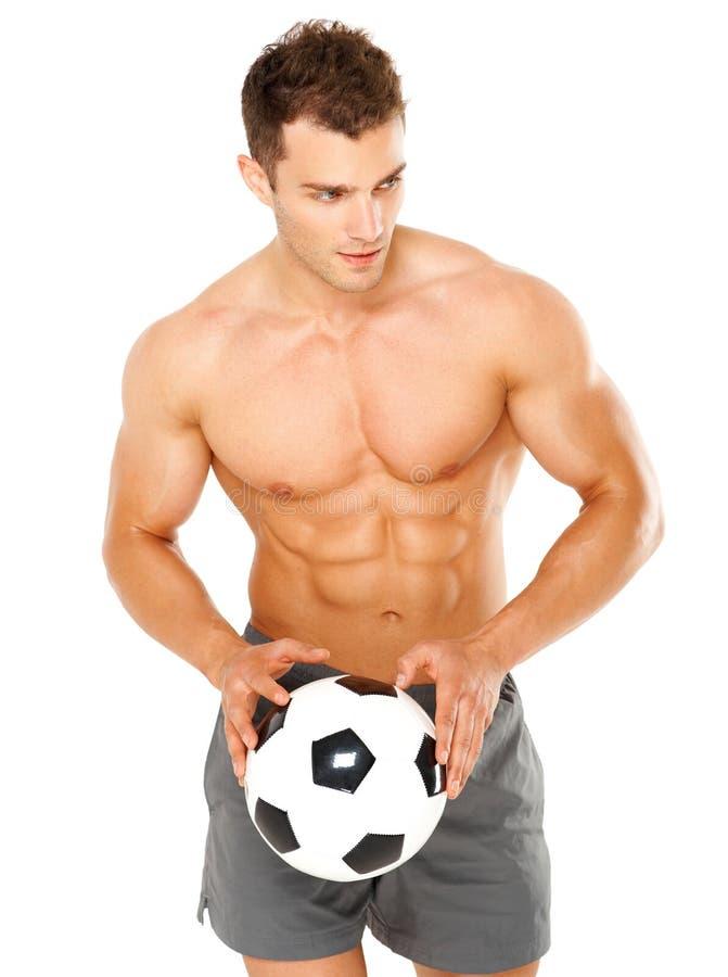 Klumpa ihop sig hållande fotboll för stilig man på vit royaltyfri foto