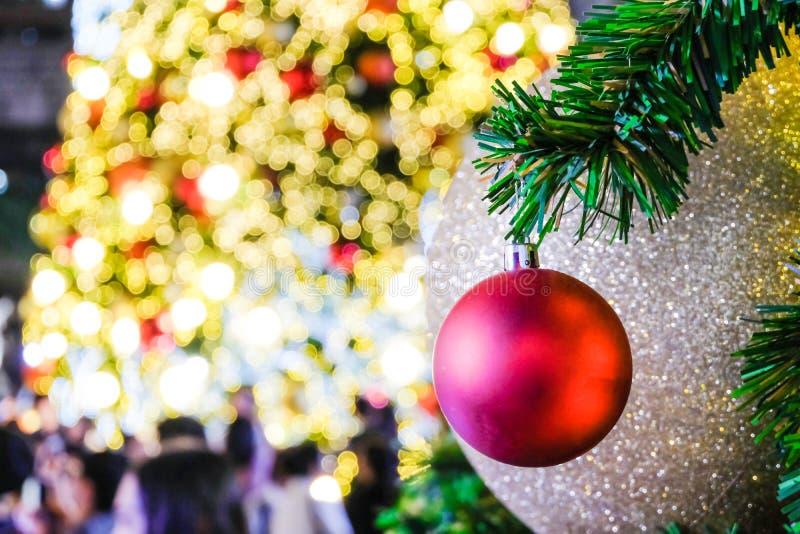 Klumpa ihop sig röd jul för närbild på framsidajulträd med suddighetsbok royaltyfria foton