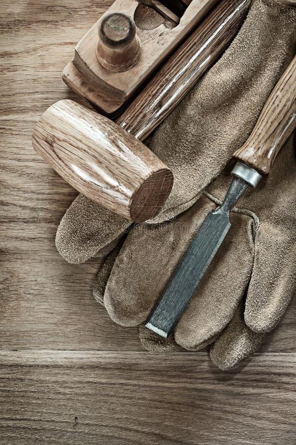 Klumpa sig hammaren som rakar skyddande handskar för plan stämjärn på träboa royaltyfri foto